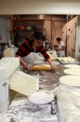 Staff at Mona's Roti in Scarborough roll and knead dough for paratha roti.