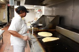 A chef at Ali's West Indian Roti Shop makes paratha on a flat-top stove.