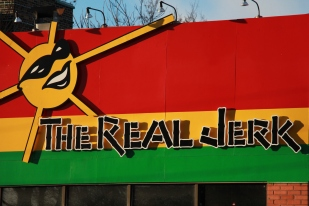 "Go to The Real Jerk during Caribana or any time year-round and you'll find some of the realest Jamaican vibes Toronto has to offer. The atmosphere here is as lively as the food. Every Thursday, they host a karaoke session aptly titled ""Irie-Okie"" and, though their old outdoor BBQs from their previous location are a thing of the past, the new location boasts a lounge area offering one of the widest selections of rums in the city, and they still host and cater an annual boat cruise event during Caribana. Prices are fair and the jerk chicken wings are the bomb. The roti comes in a generous serving, too. Originally located at Queen & Broadview in Riverdale, owners Lily and Ed Pottinger were recently forced to relocate due to construction of new condos on their old site. They've now found themselves in a bigger space at Gerrard and Carlaw. For the Pottingers, 29 years in business and a consistent place in NOW Magazine's annual Best of Toronto list doesn't mean resting on one's laurels. Ed can be seen greeting every table and clearing the dishes, and staff are helpful and knowledgeable, recommending the perfect cocktails to pair with your dish. Beautiful murals depicting scenes of Jamaica painted on sheets of zinc meanwhile have survived through three different moves (there was also a brief stint operating a smaller take out joint in suburban Woodbridge). The Real Jerk remains a landmark for the local Caribbean community and visitors to Toronto alike, attracting a culturally diverse clientele. It is a meeting place for food, culture, music and people, and truly is a piece of Jamaica in 'the Six.' Check out their sister location in Toronto's Beaches neighborhood, at the fitting address of 1004 Kingston Road."